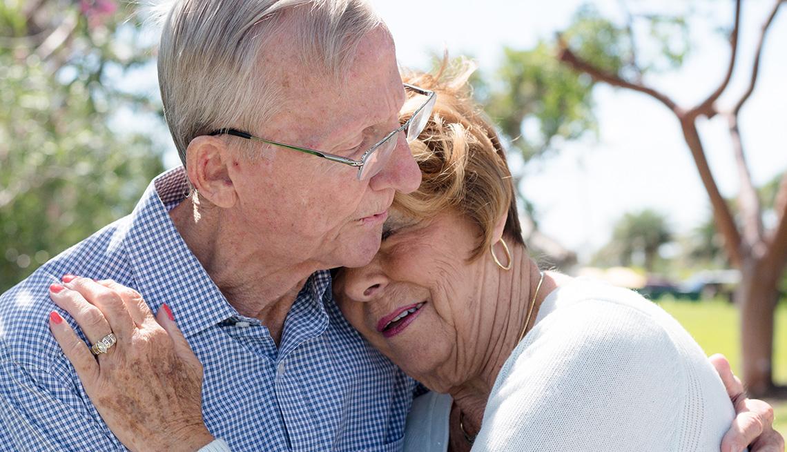 A senior couple hugging outside
