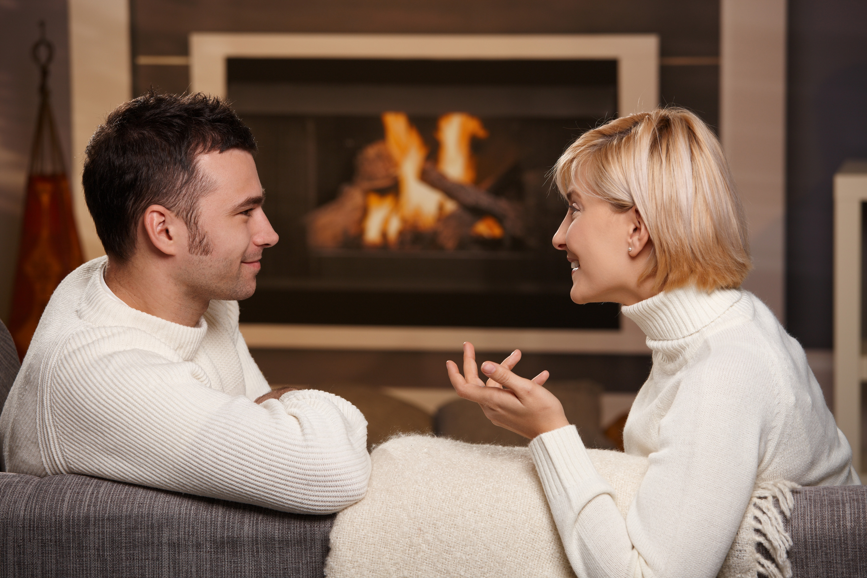 Young romantic couple sitting on sofa in front of fireplace at home, looking at each other, talking.